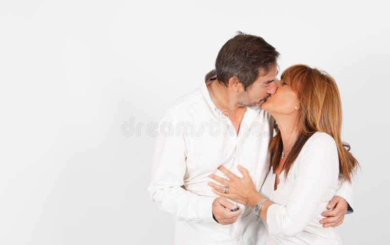 Pares maduros que dão um beijo durante uma sessão do estúdio da foto foto de stock