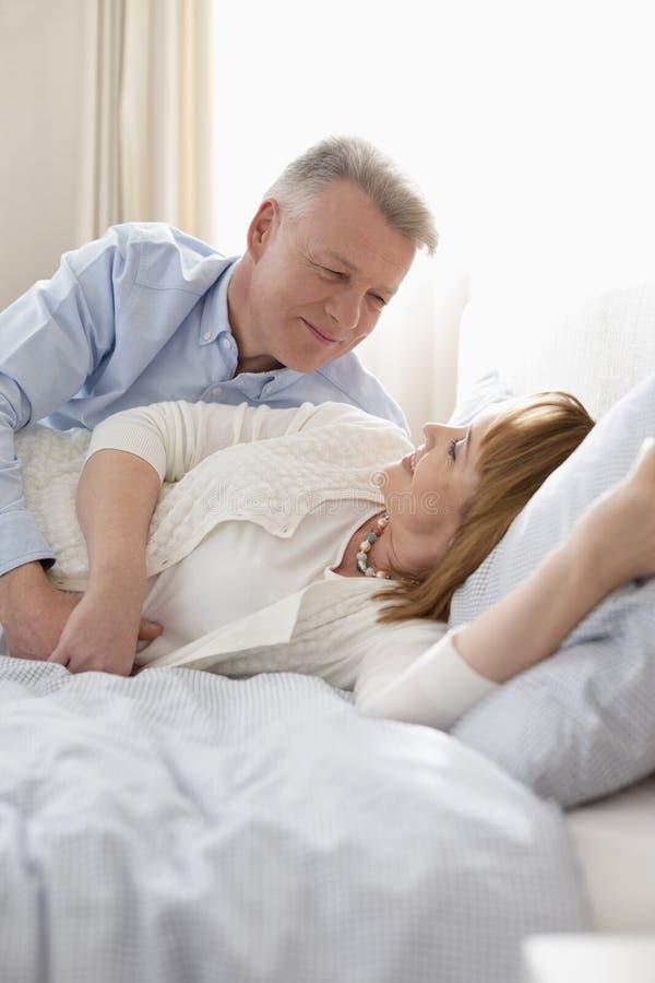 Pares maduros que encontram-se na cama em casa foto de stock royalty free
