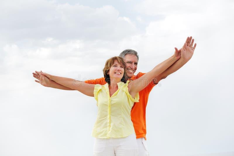 Pares maduros que estão com os braços outstretched. imagens de stock royalty free