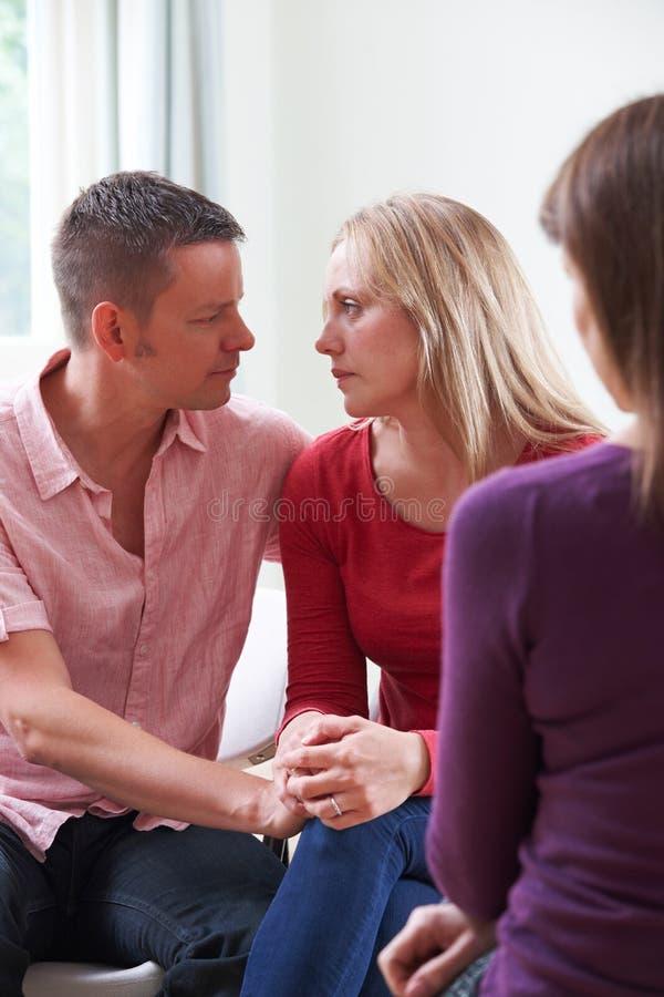 Pares maduros que falam com o conselheiro como a mulher de confortos do homem foto de stock royalty free