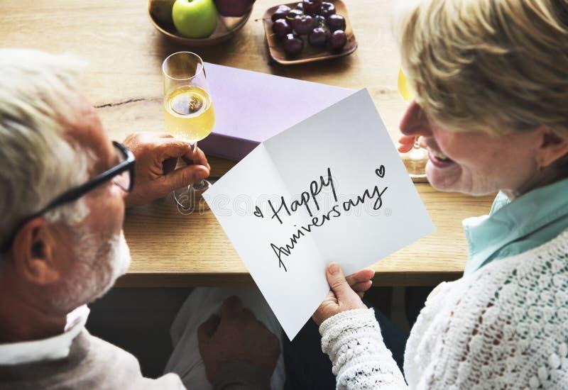 Pares maduros que guardam um cartão do aniversário foto de stock