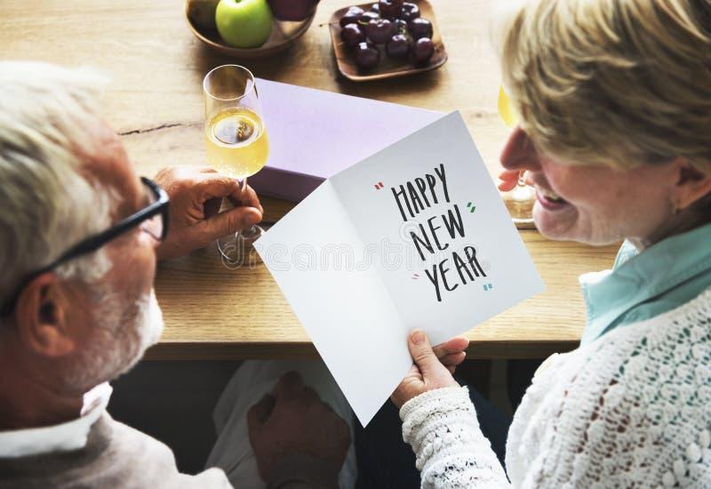 Pares maduros que guardam um cartão dos anos novos fotos de stock