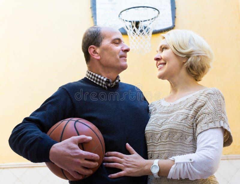 Pares maduros que jogam o basquetebol no pátio fotografia de stock royalty free