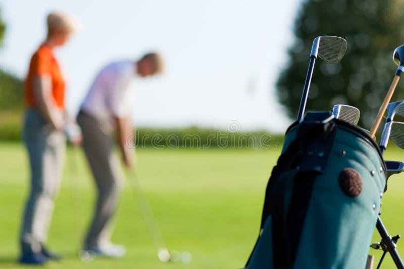 Pares maduros que juegan al golf (foco en bolso) foto de archivo