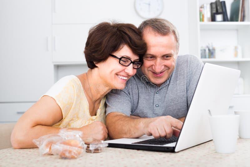 Pares maduros que miran en el ordenador portátil en casa fotografía de archivo