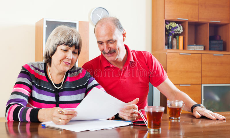 Pares maduros que olham financeiros na casa fotos de stock