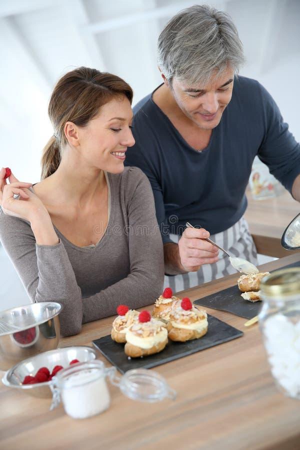 Pares maduros que preparan los pasteles en la cocina foto de archivo libre de regalías