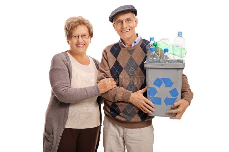 Pares maduros que presentan con una papelera de reciclaje foto de archivo
