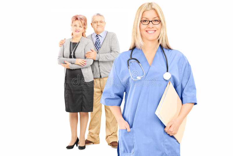 Pares maduros que presentan detrás de doctor de sexo femenino imagen de archivo