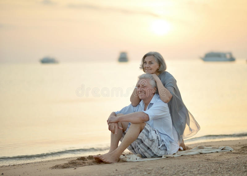 Pares maduros que relaxam na praia fotografia de stock royalty free