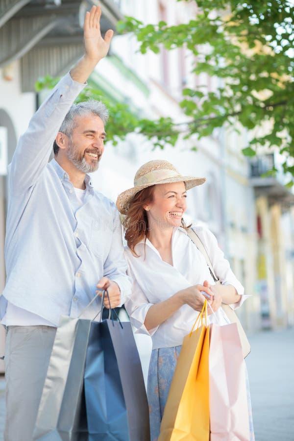 Pares maduros que retornam dos sacos de compras completos da compra, levar e acenando aos amigos imagens de stock royalty free