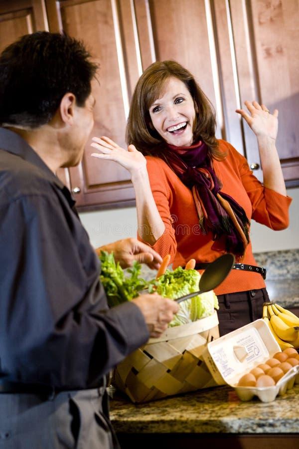 Pares maduros que se divierten el cocinar en cocina imagen de archivo