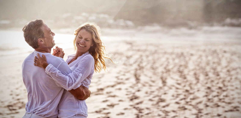 Pares maduros que se divierten junto en la playa imagen de archivo libre de regalías