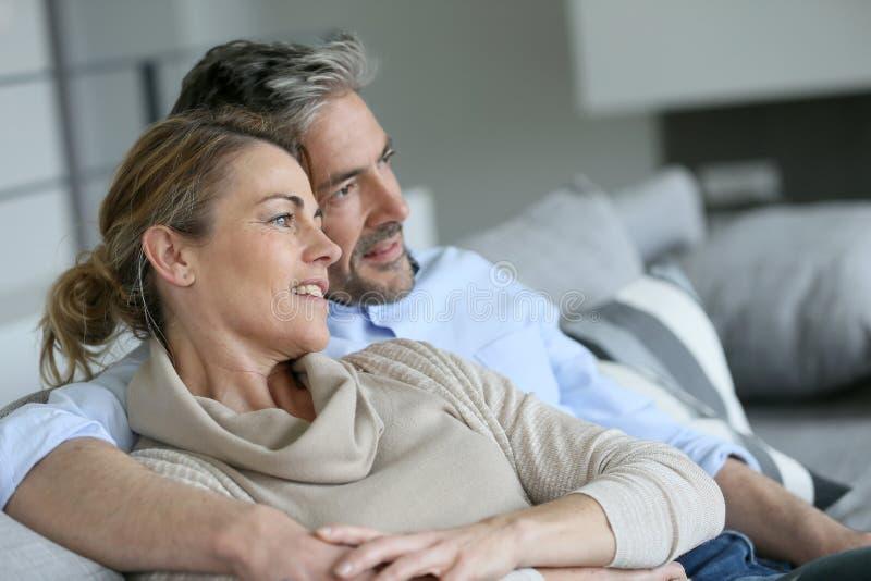 Pares maduros que sentam em casa o relaxamento imagem de stock royalty free