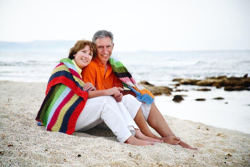 Pares maduros que sentam-se na praia. fotos de stock royalty free