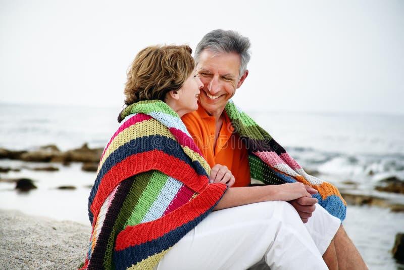 Pares maduros que sentam-se na praia. imagens de stock royalty free