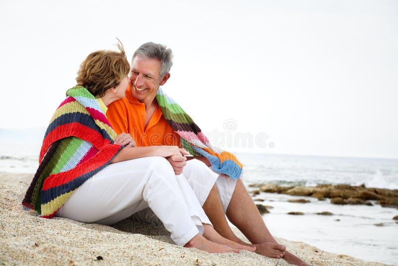 Pares maduros que sentam-se na praia. fotografia de stock royalty free
