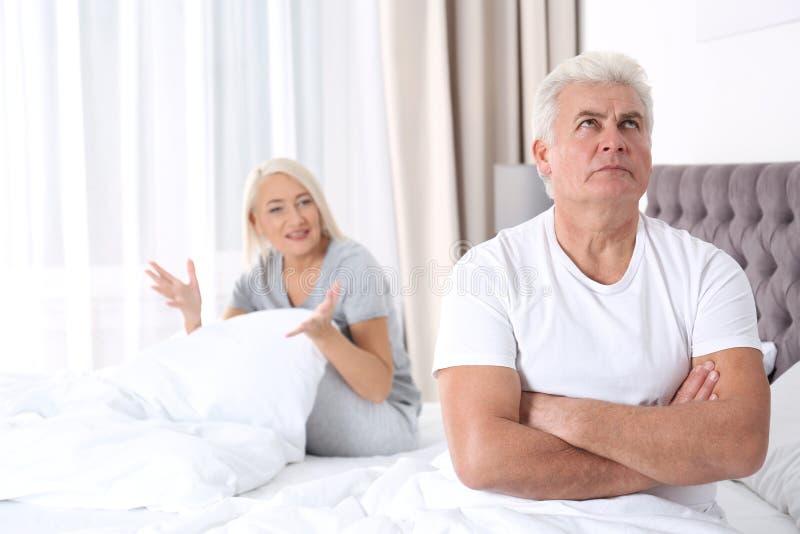 Pares maduros que têm o conflito no quarto em casa imagens de stock