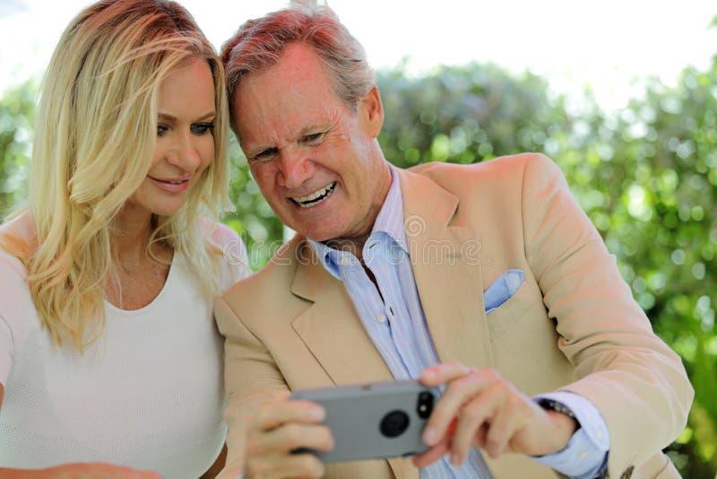Pares maduros que tomam selfies no telefone imagens de stock royalty free