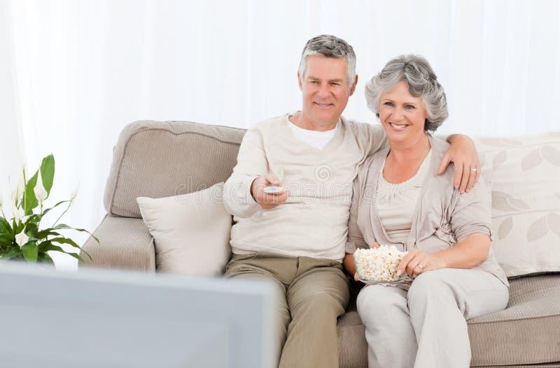 Pares maduros que ven la TV en su sala de estar imagen de archivo