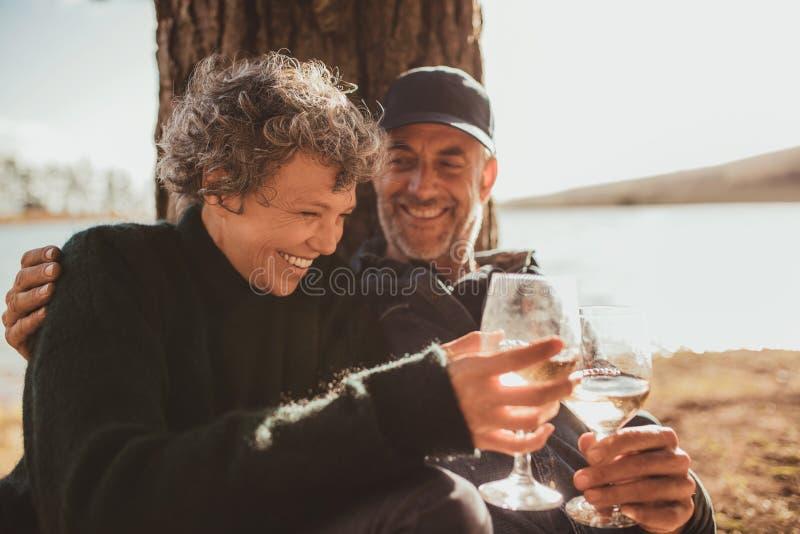 Pares maduros relaxado que comem um vidro do vinho no acampamento foto de stock