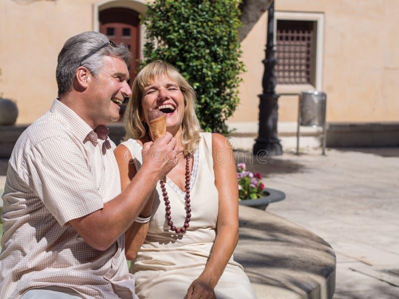 Pares maduros románticos felices que se ríen de una buena broma con helado fotografía de archivo libre de regalías