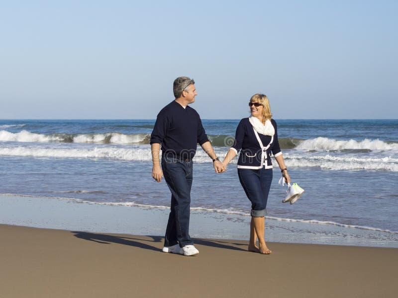 Pares maduros románticos que caminan a lo largo de la playa imagenes de archivo