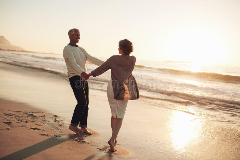 Pares maduros românticos que apreciam um dia na praia imagens de stock