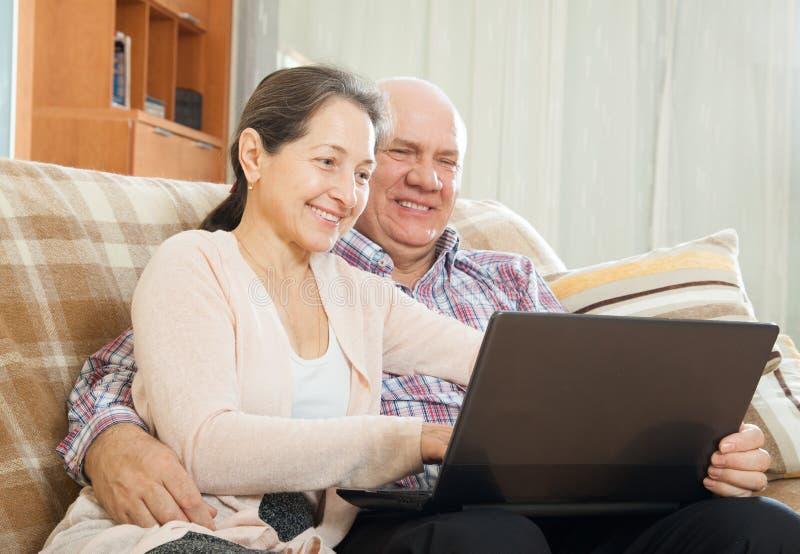 Pares maduros usando o portátil em casa foto de stock