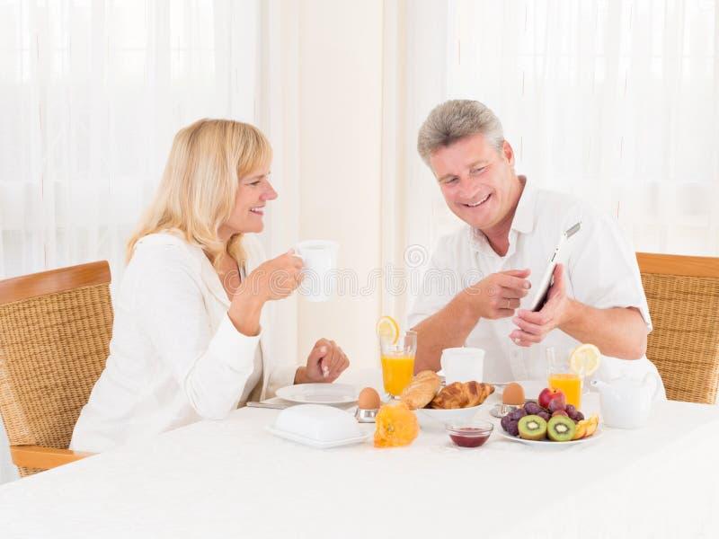 Pares maduros usando-se e apontando em um tablet pc ao apreciar seu café da manhã saudável foto de stock