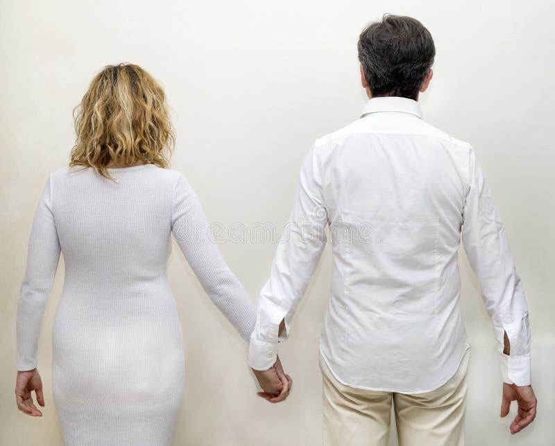 Pares maduros vestidos em branco atrás de guardar as mãos contra um fundo branco imagem de stock