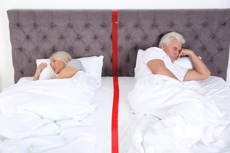 Pares maduros virados com os problemas do relacionamento que encontram-se separadamente fotografia de stock royalty free