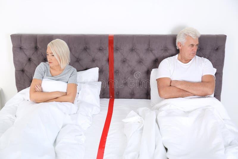 Pares maduros virados com os problemas do relacionamento que encontram-se separadamente na cama imagens de stock