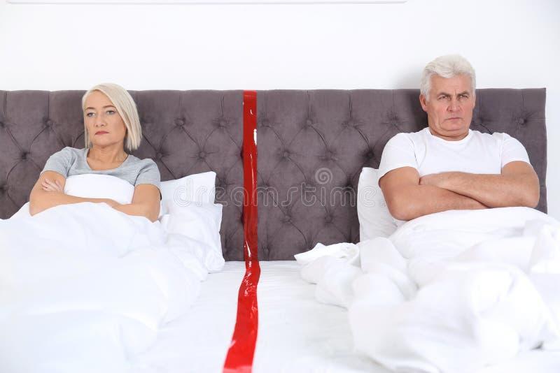 Pares maduros virados com os problemas do relacionamento que encontram-se separadamente na cama imagens de stock royalty free
