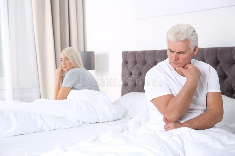 Pares maduros virados com os problemas do relacionamento que sentam-se na cama fotografia de stock royalty free