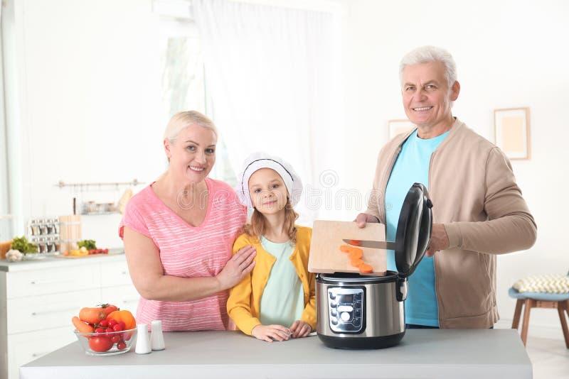 Pares maduros y su nieta que preparan la comida con la cocina multi moderna fotografía de archivo