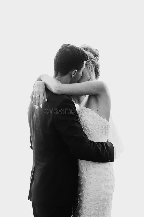 Pares magníficos de la boda de los recienes casados que abrazan mientras que teniendo primera danza en el fondo blanco Novia feli imagen de archivo