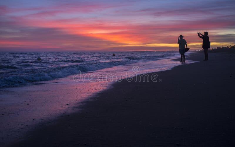 Pares mais velhos do turista que tomam imagens na praia de Islantilla durante imagem de stock