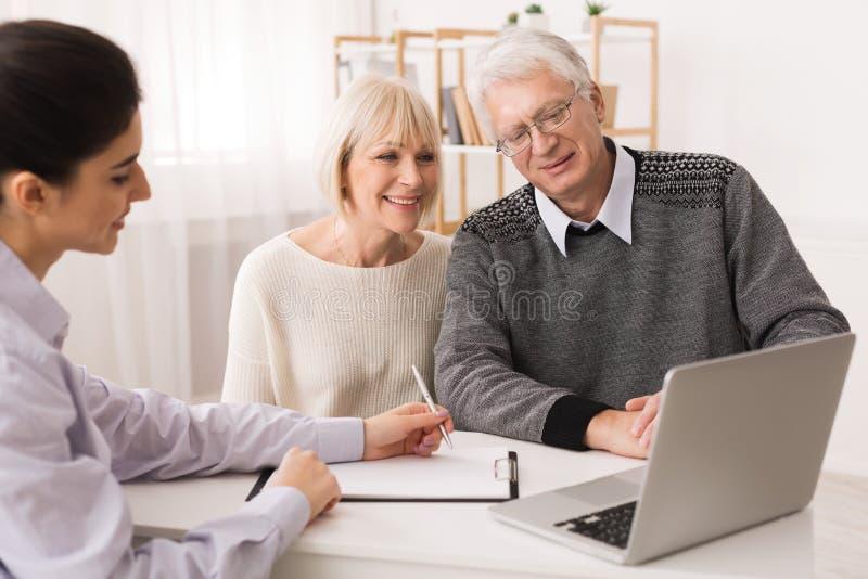 Pares mais velhos que consideram a compra nova da casa que olha o portátil foto de stock