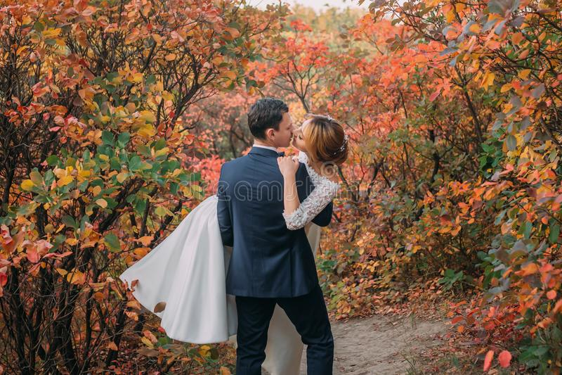 Pares maravillosos en día de boda novia en vestido largo blanco elegante y ramo azul a disposición, novio en un de moda azul fotos de archivo libres de regalías