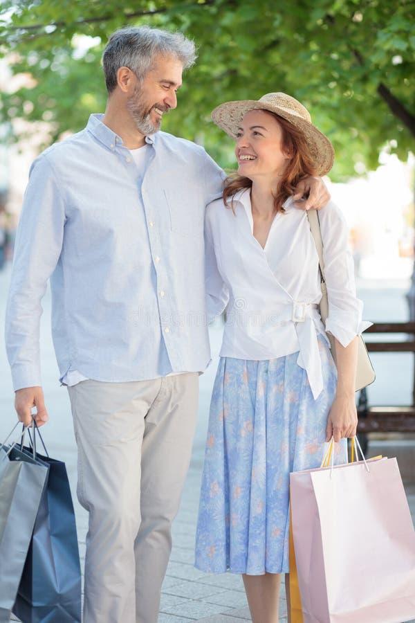 Pares, marido feliz y esposa maduros volviendo de compras foto de archivo