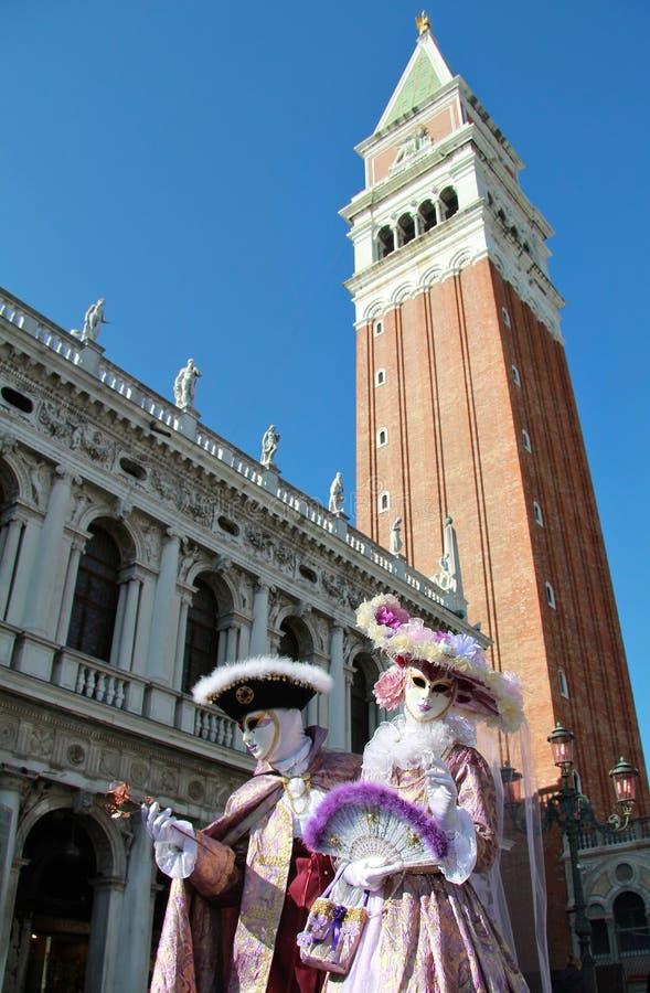 Pares mascarados nobres sob a torre de Bell de San Marco foto de stock