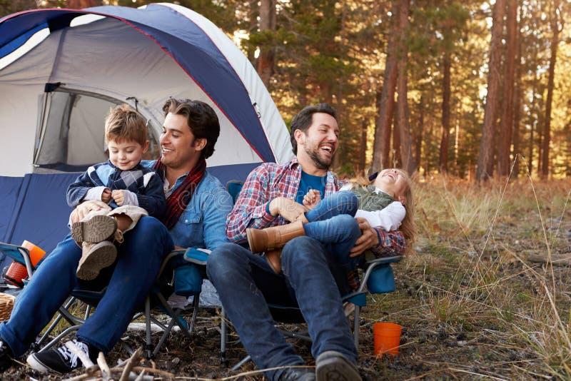 Pares masculinos alegres com as crianças na viagem de acampamento imagem de stock royalty free