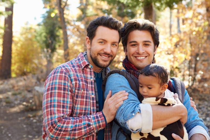 Pares masculinos alegres com o bebê que anda através da floresta da queda fotografia de stock royalty free
