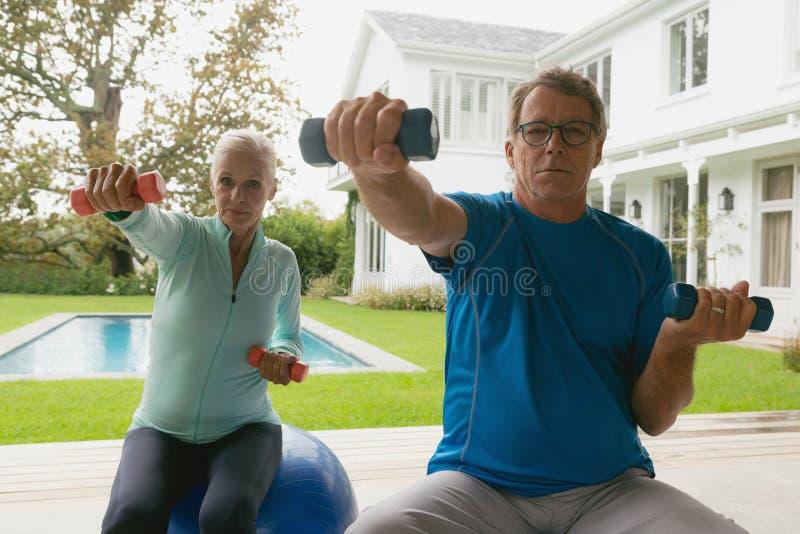Pares mayores activos que ejercitan con pesa de gimnasia en pórtico en casa imagen de archivo
