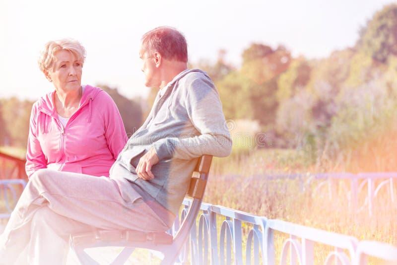 Pares mayores activos que hablan mientras que descansa sobre banco en el parque imagen de archivo