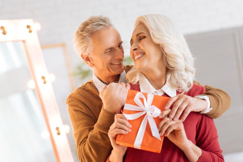 Pares mayores adorables con el regalo que abraza firmemente imagen de archivo libre de regalías