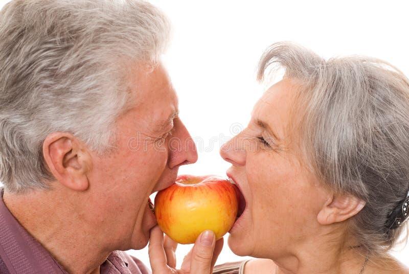 Pares mayores agradables que comen una manzana foto de archivo