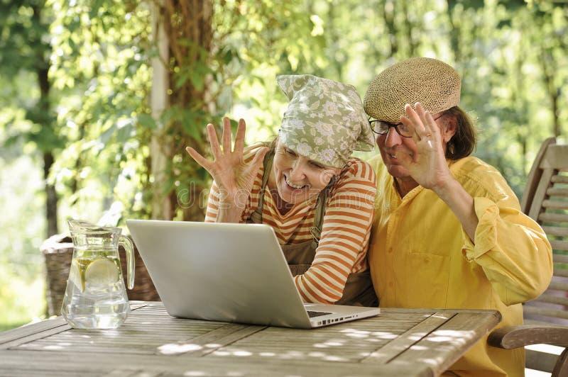 Pares mayores al aire libre con el ordenador portátil imagenes de archivo