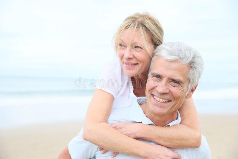 Pares mayores alegres en la playa imagenes de archivo